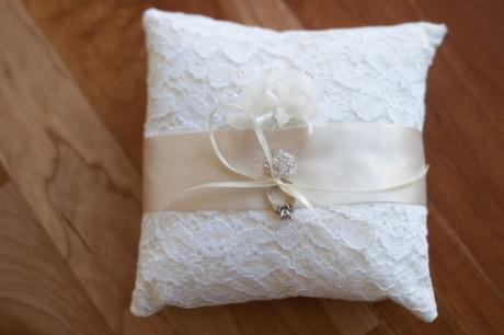 A white and ivory lace ring pillow with a diamante trim for flower girls and pageboys.