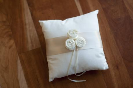 A cotton wedding ring cushion with three ivory silk flowers and ribbon to hold the wedding rings.