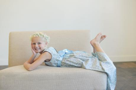 A young flower girl lying on a sofa wearing a pretty blue floral bridesmaid dress with a blue satin sash.