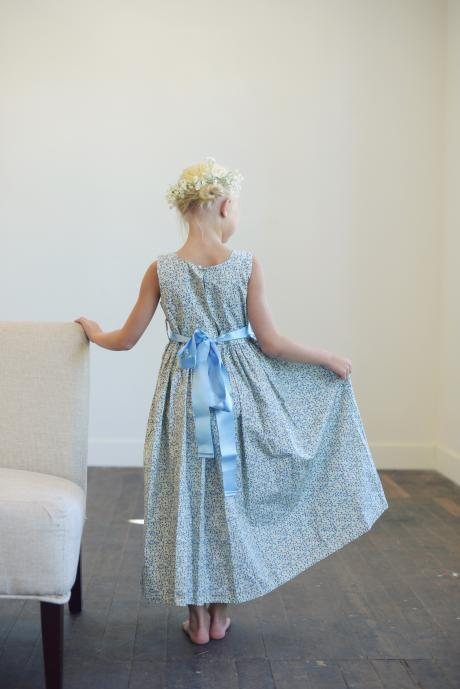 A flower girl wearing a light blue floral flower girl dress in a pretty pattern with a blue satin sash.