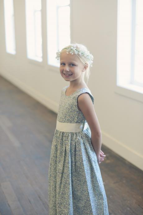 A young flower girl wearing a blue floral flower girl dress with an ivory satin sash. The dress is available in many different prints.