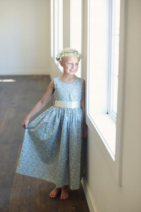 A junior bridesmaids standing by a window wearing a blue floral flower girl dress with an ivory sash.