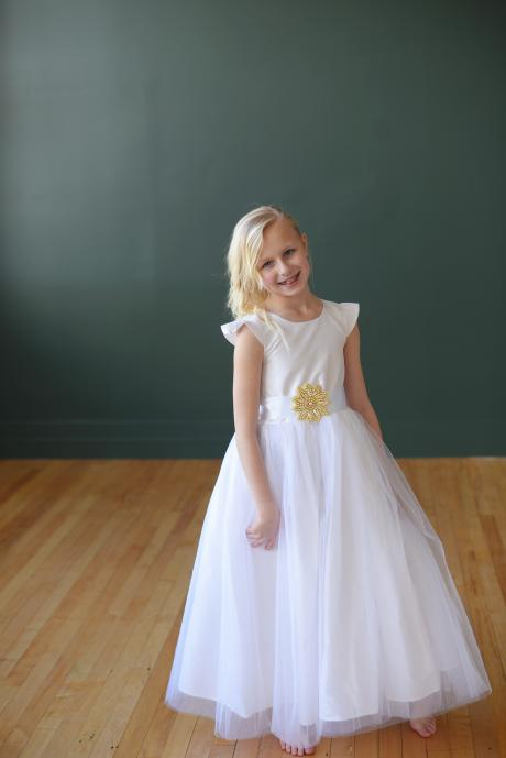 A young girl in a flower girl dress with  pretty butterfly sleeves and gold diamanté motif on the belt.