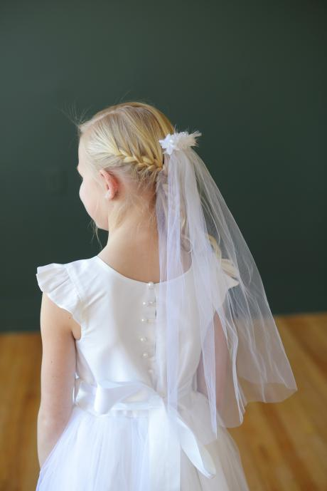 A young girl in a white first communion dress with a full tulle skirt, white silk bodice, diamanté sash and communion veil.