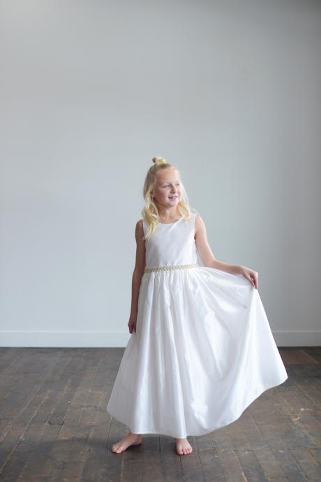 A flower girl holding the skirt of her white silk dress with pearls at the waist.