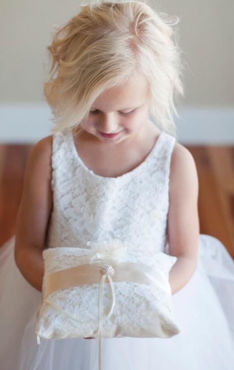 A flower girl wearing a lace and ivory tulle flower girl dress and holding a ring pillow for a wedding.