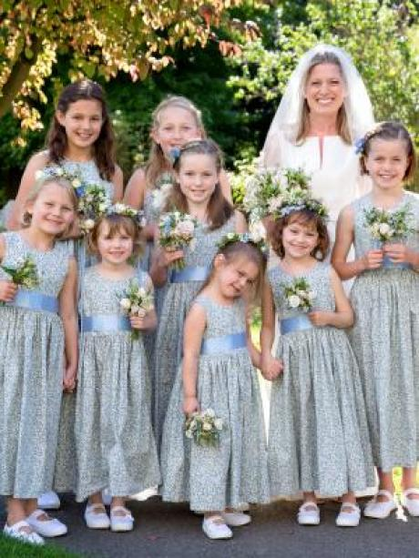 A group of flower girls and a bride wearing blue floral ankle length flower girl dresses with white shoes and ivory sashes.