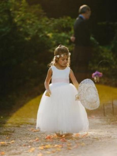 A girl walking on a country road in an ivory flower girl dress with a baby pink sash. She is holding a flower girl basket.