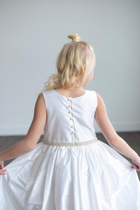 The back of a girl taking her first communion wearing a white silk first communion dress with a wide band of pearls at the waist.