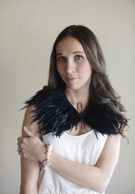 A bride wearing a flower girl or bridesmaid black feather shawl at a wedding.