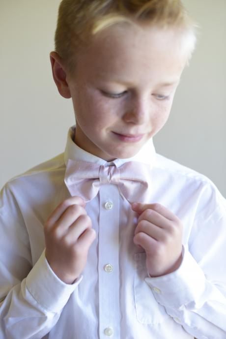A pageboy wearing a pure silk bow tie at a wedding in blush pink.