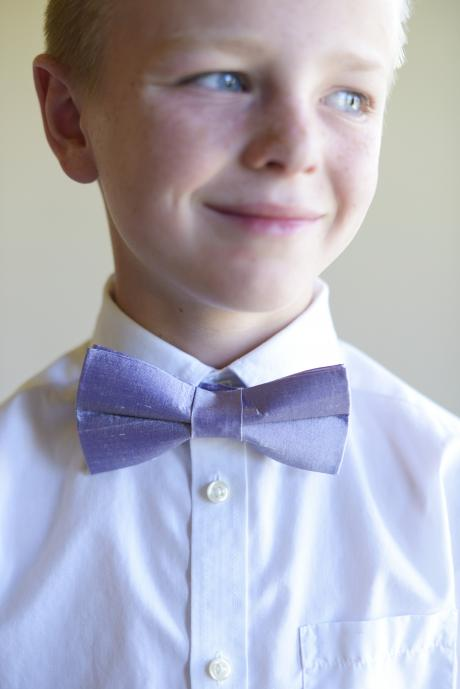 A close up of a boy wearing a pre-ties bow tie at a wedding, in lilac silk.