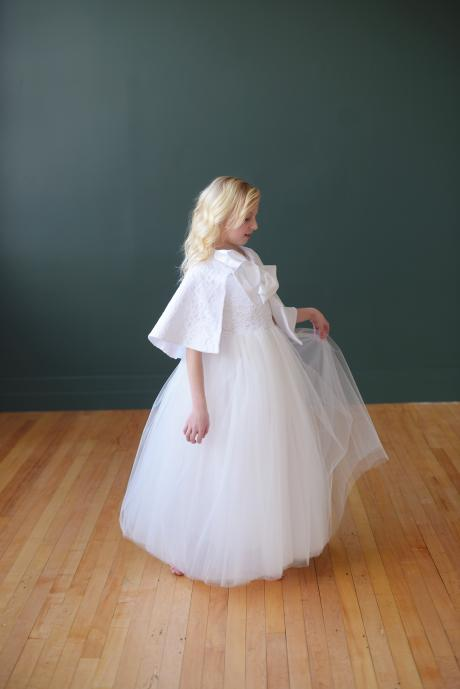 A girl wearing a white first communion dress and a pretty  lace cape