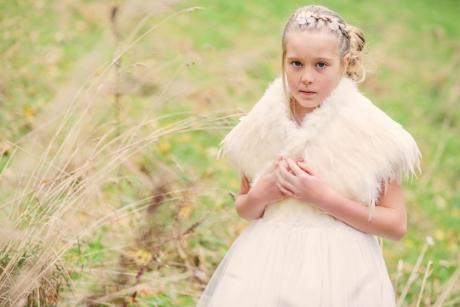A young flower girl standing in a field wearing an ivory flower girl dress and an ivory feathered wedding cape