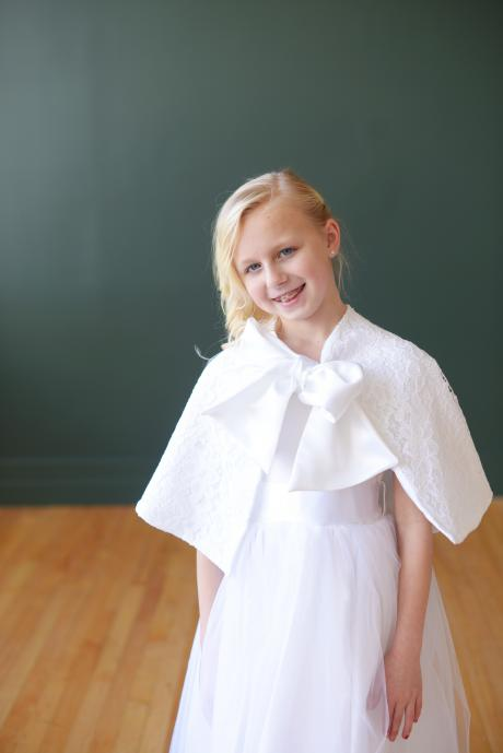 A girl wearing a white lace first communion cape which ties at the front with a big bow