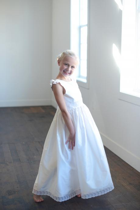 A girl standing by a window wearing a white silk first communion dress with a lace hem