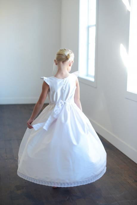 A photo of the back of a girl wearing a silk and lace first communion dress
