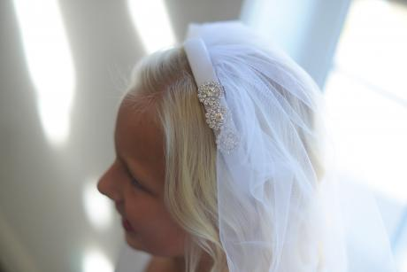 A girl wearing a handmade white tulle veil for first communion