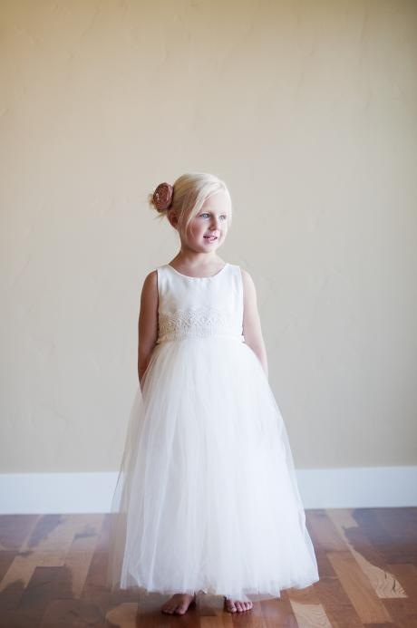 A girl with her arms behind her back wearing a made to measure ivory cotton flower girl dress with lace belt, tulle skirt and pink flower.