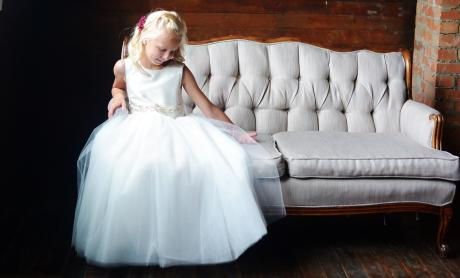 A photo of  girl sitting on a sofa at a wedding wearing a communion dress with a white sash