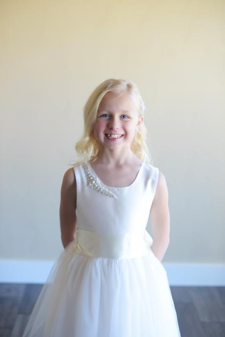 A girl at  wedding wearing a silk and tulle flower girl dress with a [earl trim on the shoulder