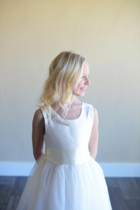 A first communion dress in white with diamanté trim and a tulle skirt