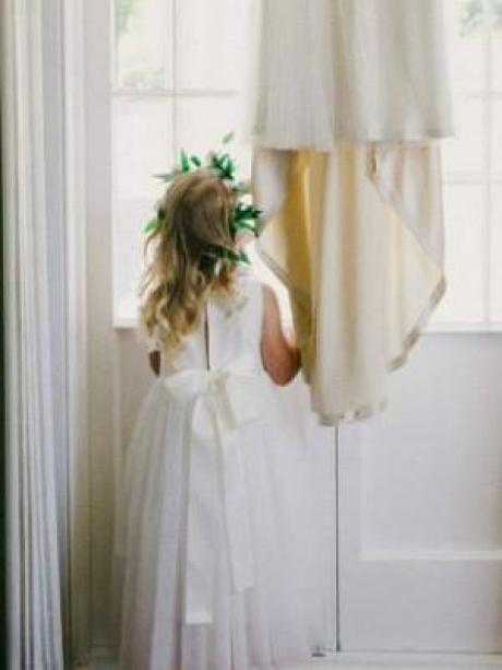 A young flower girl standing at a window wearing a designer ankle length flower girl dress in ivory cotton with blush pink flower on the belt.
