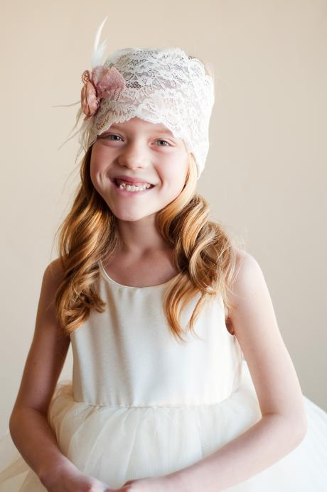A 10 year old girl wearing an ivory flower girl dress with a lace flower girl and junior bridesmaid headband with pink flower.