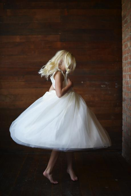 A flower girl spinning and showing the ankle length full tulle skirt, butterfly sleeves and sash.