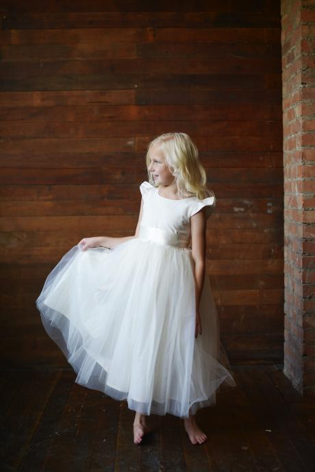 A girl wearing a bespoke junior bridesmaid flower girl dress with butterfly sleeves, tulle skirt and a ribbon sash in ivory.