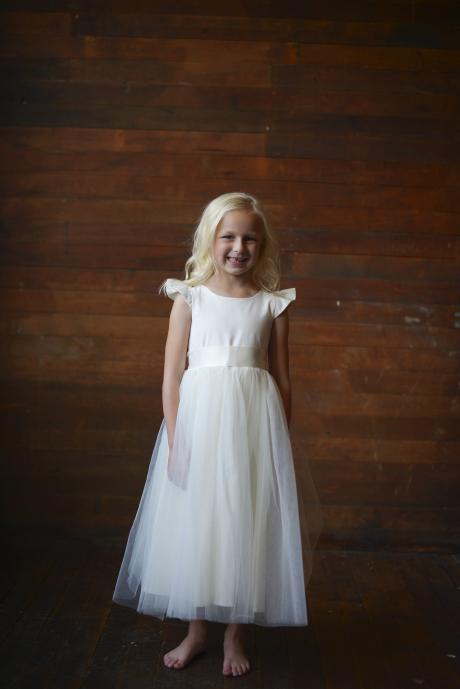 A 6 year old girl at a wedding wearing an ankle length ivory flower girl dress with a tulle skirt, butterfly sleeves and silk bodice.