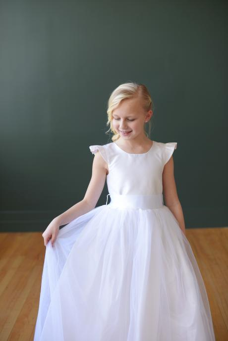 A 7 year old girl wearing a white, silk first communion dress with diamanté sash, tulle skirt and butterfly sleeves.
