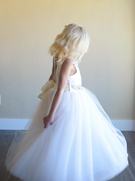 A side view of a girl wearing a bespoke white tulle dress with diamanté on the shoulder and at the waist.