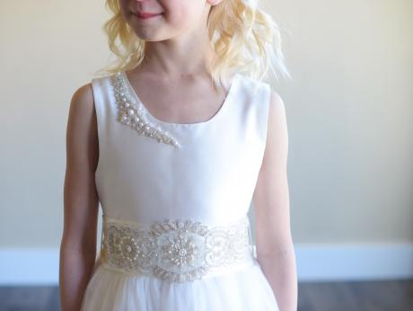 A flower girl wearing a bespoke white silk and tulle dress with a diamanté sash and diamanté on the shoulder.