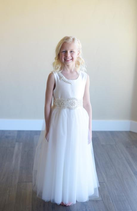 A girl taking her first communion wearing a white silk dress with a tulle skirt and diamanté motifs at the shoulder and on the waist.