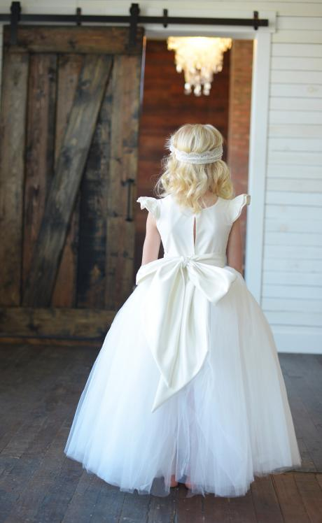 The back view of a girl wearing a flower girl dress with a sweetheart neckline, very full tulle skirt and a big white bow. The dress has a sweetheart neckline.