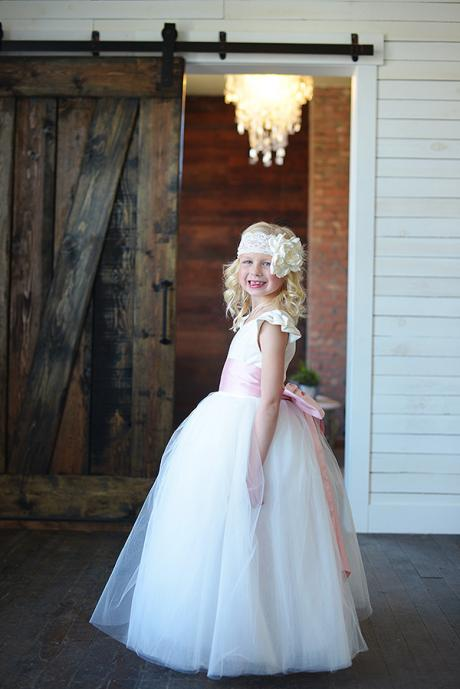A side view of a girl wearing a white and ivory junior bridesmaid dress with a wide pink bow and very full tulle skirt. The dress has butterfly sleeves and a sweetheart neckline.