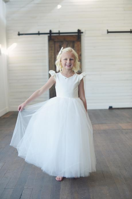 A girl wearing a bespoke flower girl dress in white with a very full tulle skirt, butterfly sleeves and a sweetheart neckine.