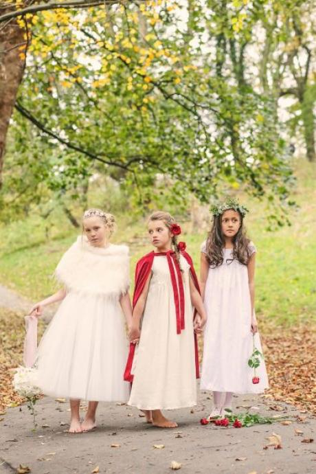 A group of flower girls in a field wearing a wedding shawl with a red flower girl dress and a red flower girl cape.