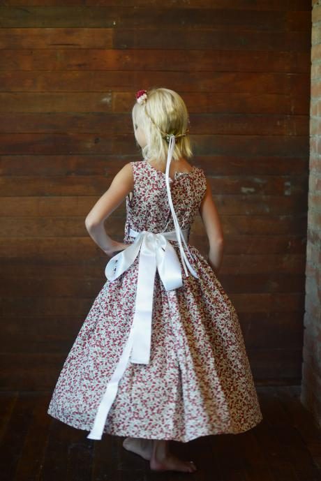 A photo showing the back of a strawberry print dress with an ivory sash and big bow
