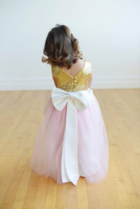 A flower girl wearing a gold sequin and pink tulle flower girl dress with a white sash and big bow.