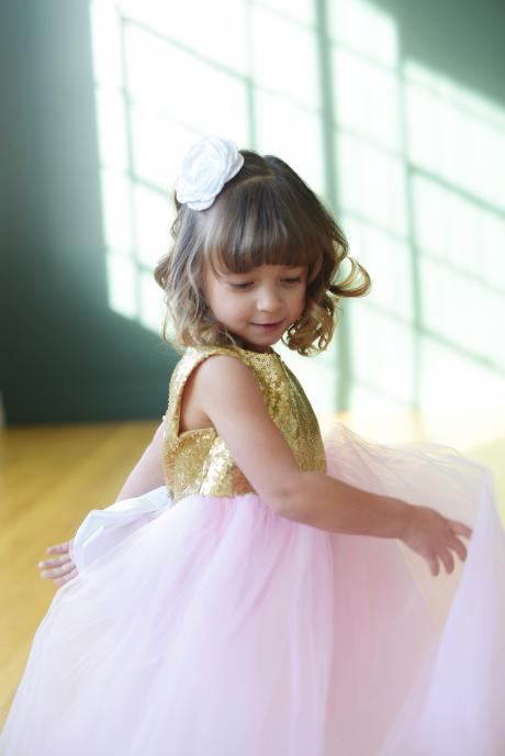 a little flower girl and  junior bridesmaid and a wedding wearing a pink and gold sequin flower girl dress