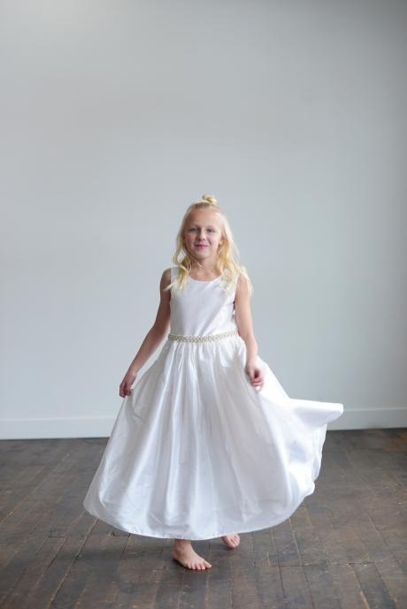 A young girl wearing a pure white silk flower girl dress with pearl embellishments at the waist and full skirt.