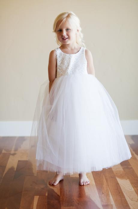 A young flower girl wearing a white lace and tulle flower girl dress.