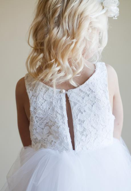 The back of a lace and white tulle flower girl dress with delicate pearl button at the top.