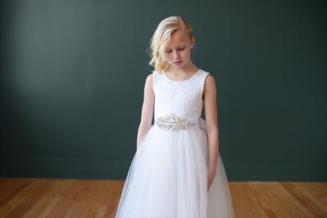 A flower girl standing against a green background wearing a full length lace and white tulle flower girl dress. These dresses are handmade in London, UK.