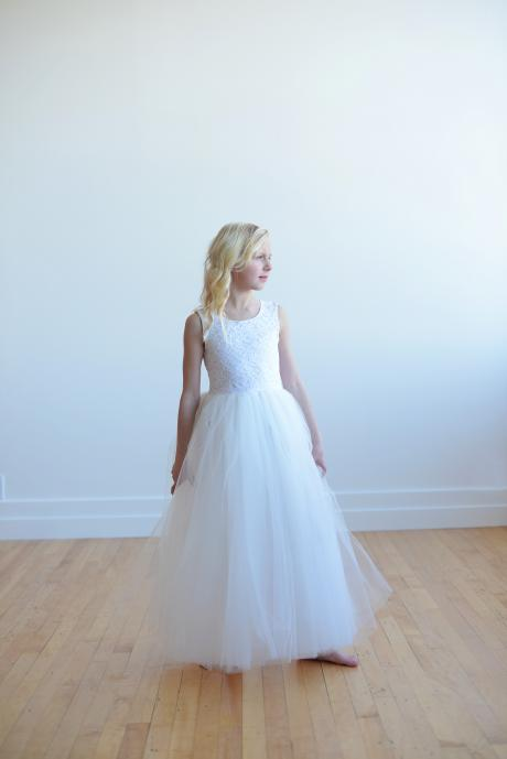 A flower girl wearing a floor length dress with an ivory lace bodice and full tulle skirt. These dresses are handmade in London, UK.