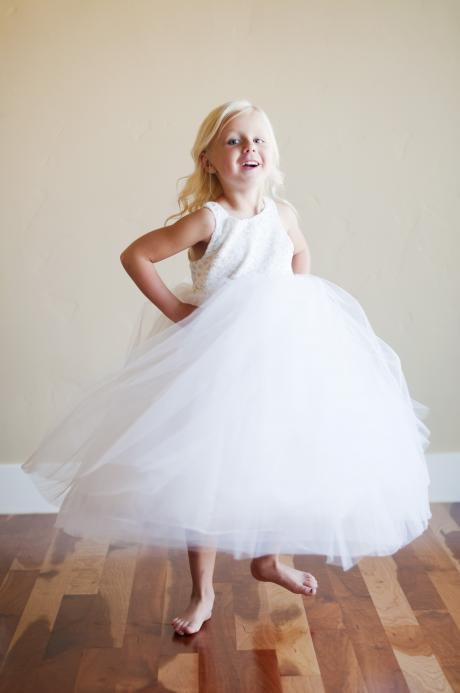 A young girl spinning in her flower girl dress which has a lace bodice and full tulle skirt.