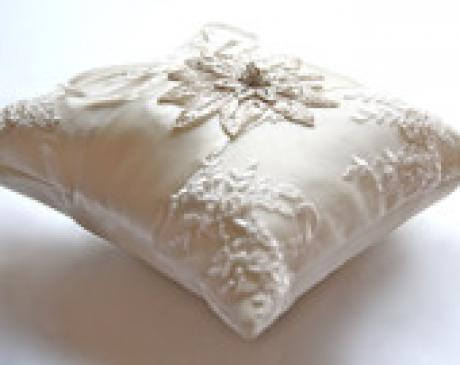 A beaded lace ring pillow held by a flower girl in ivory with a star motif. The ring pillow is made of exquisite wedding lace with a  diamante motif nd ribbons to hold the wedding rings.