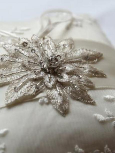 A beaded lace wedding ring pillow with star motif for wedding rings.